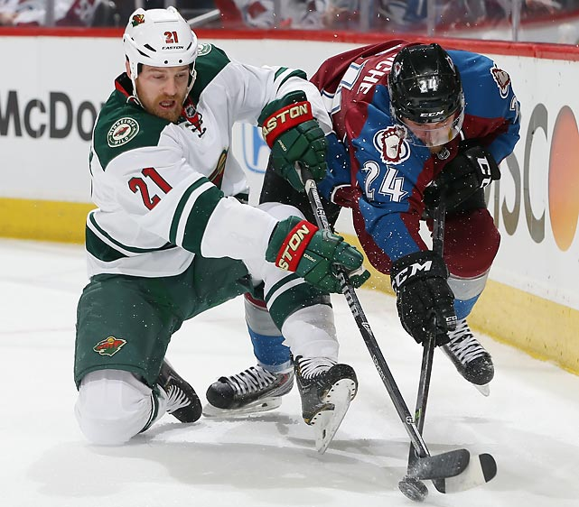 Kyle Brodziak of the Minnesota Wild and Marc-Andre Cliche of the Colorado Avalanche fight for the puck.