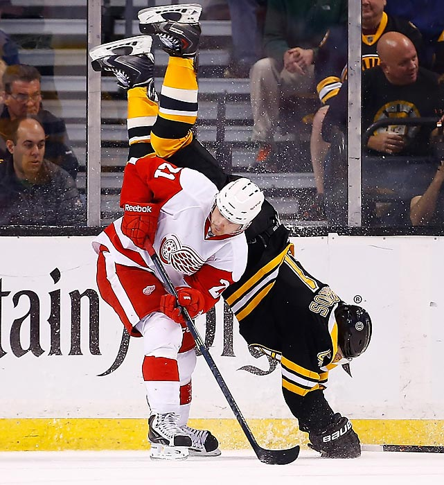 Andrej Meszaros of the Boston Bruins flips over Tomas Tatar of the Detroit Red Wings.
