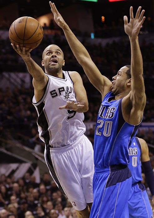 San Antonio Spurs guard Tony Parker flips a shot over Devin Harris of the Dallas Mavericks during Game 1 of their first-round series.