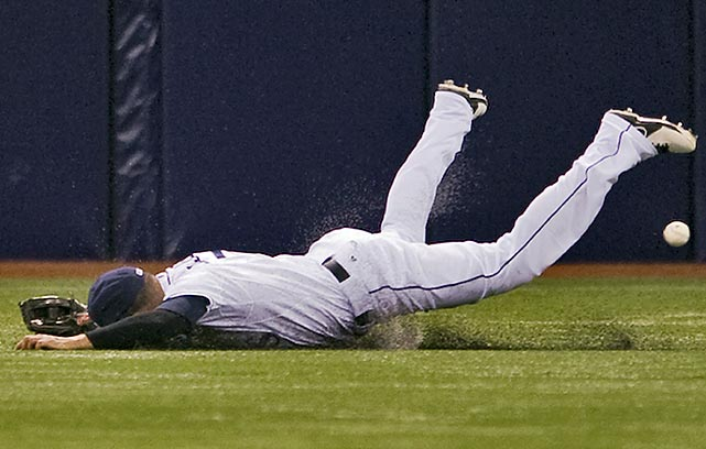 Tampa Bay Rays outfielder David DeJesus takes a rough landing after failing to corral what became a three-run double by Scott Sizemore of the New York Yankees.