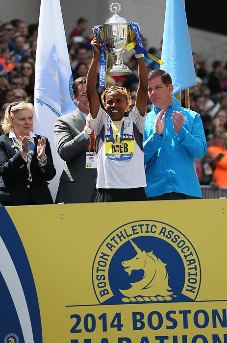 After winning the marathon, Keflezighi hoists the trophy.
