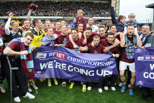 Burnley celebrates its promotion to the Premier League after topping Wigan on Monday.