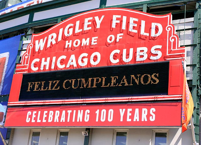 "All decked out for the celebration of its 100th Birthday, Wrigley's sign, crudely translated, means ""Abandon all hope ye who enter here."""