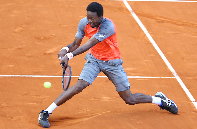 After a rain delay, Gael Monfils easily defeated qualifier Ricardas Berankis 6-1, 6-3.