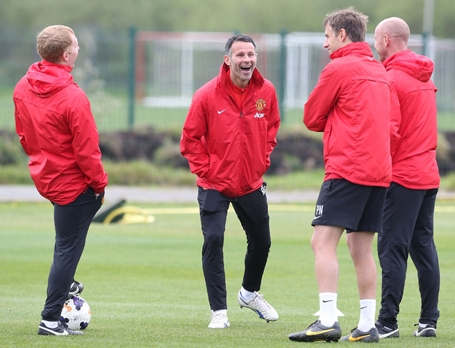 Ryan Giggs, center, jokes with former teammates-turned-assistant coaches Paul Scholes, Phil Neville and Nicky Butt at Manchester United training.