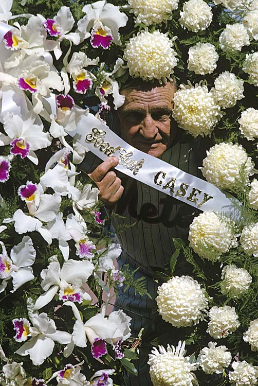 New York Mets manager Casey Stengel poses in a bed of flowers before the first regular season game at Shea Stadium.