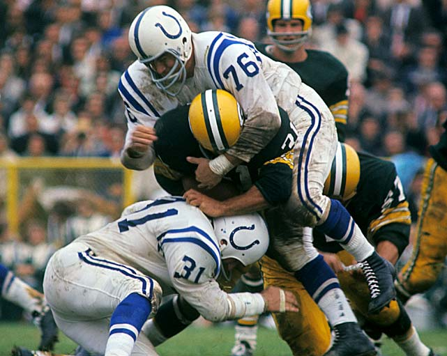 Steve Stonebreaker (31) and Fred Miller (76) of the Baltimore Colts tackle Jim Taylor of the Green Bay Packers at City Stadium in Green Bay.