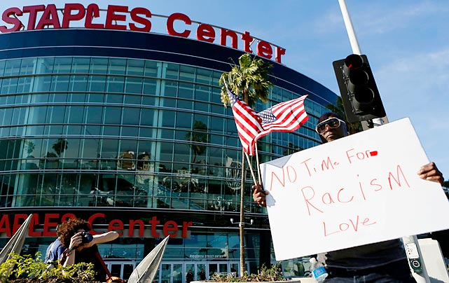 A fan outside the Staples Center holds a sign in protest of Donald Sterling's racist attitude.