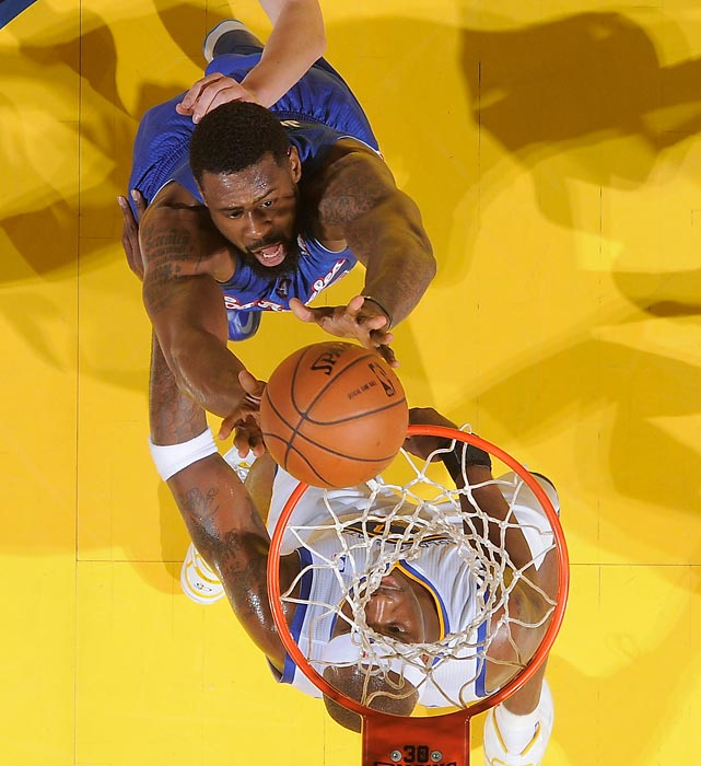 DeAndre Jordan of the Los Angeles Clippers grabs a rebound over Klay Thompson (top) and Jermaine O'Neal of the Golden State Warriors in Game 3 of a Western Conference quarterfinals.