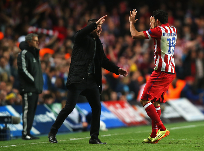 Atletico Madrid manager Diego Simeone greets Diego Costa with a high five after his penalty kick, with Chelsea manager Jose Mourinho, left, unable to watch.