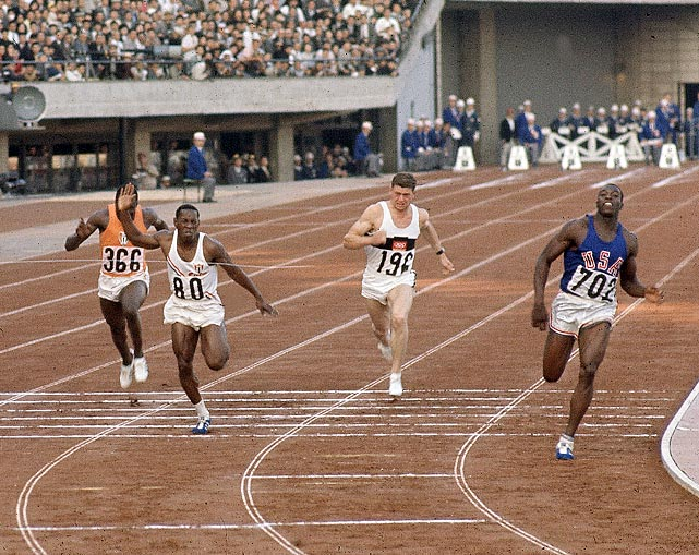 American sprinter Bob Hayes ties the world record in the 100-meter dash with a 10.06 clocking in the final at the 1964 Olympics in Tokyo.