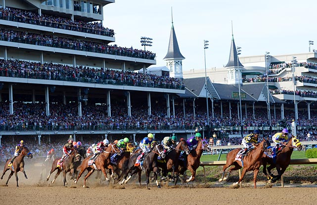 Horses round a turn at the Kentucky Derby. Eventual winner California Chrome sits by the rail in third place.