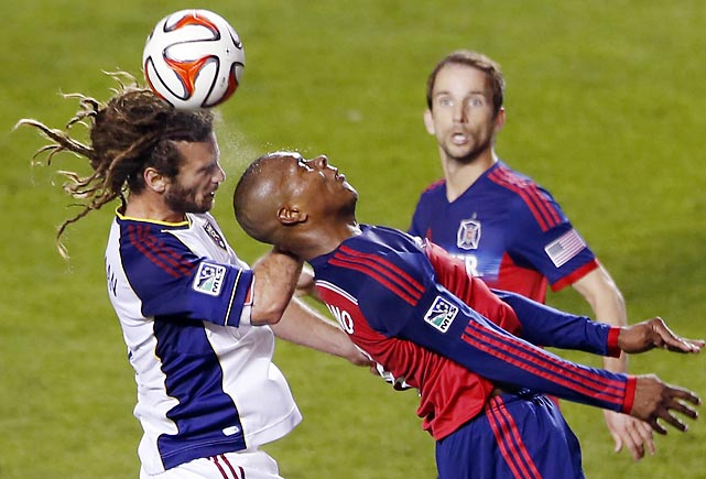Real Salt Lake midfielder Kyle Beckerman, left, heads the ball against Chicago Fire forward Juan Luis Anangono as Mike Magee looks on.