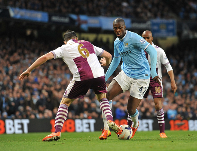 Yaya Toure (42) goes at Ciaran Clark in Manchester City's 4-0 win over Aston Villa on Wednesday.