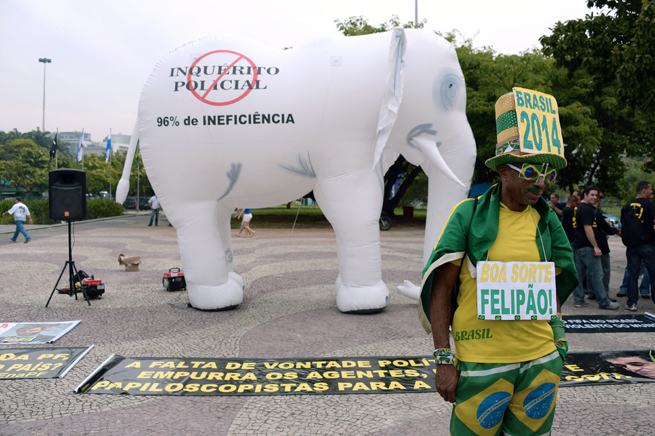 A fan poses outside of the building where Brazil announced its World Cup roster as part of a protest on Wednesday.