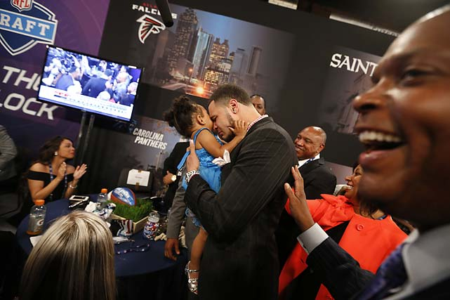 Mike Evans, from Texas A&M, holds his 2-year-old daughter Mackenzie as he reacts after being selected seventh overall by the Tampa Bay Buccaneers.