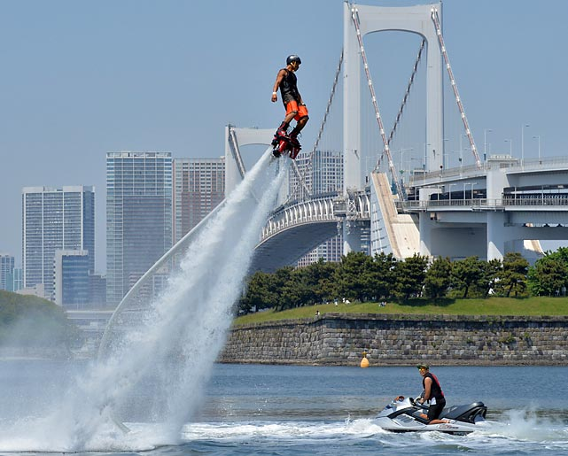 A rider on a water-propelled flyboard in Tokyo has ignition of the power shoes as he reenacts Rebus Kaneebus' legendary leap to the center of the Earth.