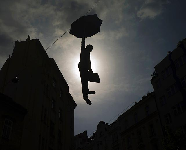 "A sculpture by Czech Artist Michal Trpak features a businessman with a bumbershoot floating above a street in Prague. According to Trpak the work ""is a paraphrase of the economic crisis."" Perhaps you know the feeling."