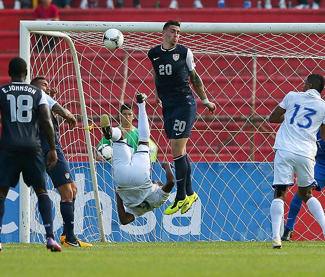 Juan Carlos Garcia of Honduras (falling), hits a remarkable bicycle kick past U.S. defender Geoff Cameron. The U.S. dropped its Hexagonal opener 2-1 on Feb. 6, 2013, in San Pedro Sula, Honduras.