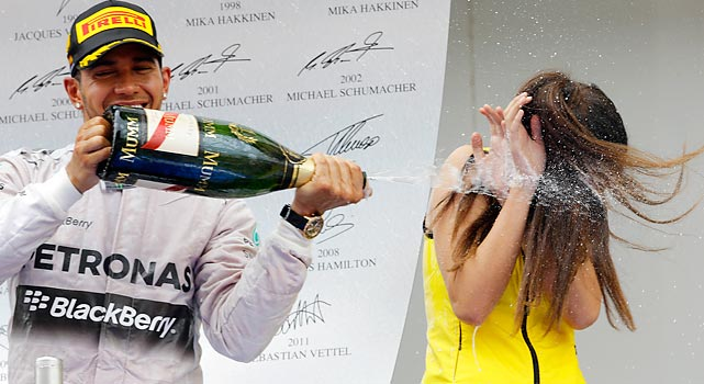 "If you've ever wondered, as we have, what ""Formula One"" is, it appears to be some kind of mysterious liquid, like Grecian Formula or Baby Formula, that comes in a bottle. Here we have driver Lewis Hamilton applying some on an innocent bystander after winning the Spanish Grand Prix."
