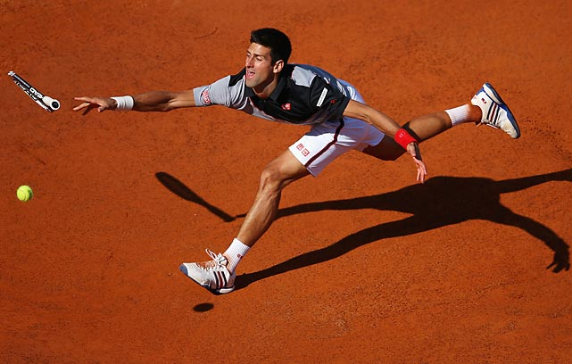 Novak Djokovic of Serbia tosses his racket at the ball while taking on Milos Raonic of Canada at the Internazionali BNL d'Italia in Rome.