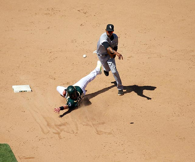 Alexei Ramirez of the Chicago White Sox turns two and avoids a sliding Josh Donaldson of the Oakland Athletics.