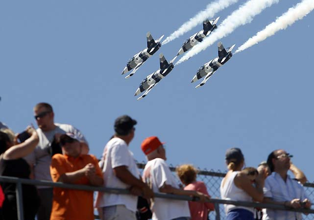 Fans watch as four L-39 Albatros high-performance jet trainer aircraft flown by the Black Diamond Jet Team, a civilian-owned aerobatic jet team, perform a fly-over during the National Anthem before the start of the 98th running of the Indianapolis 500.