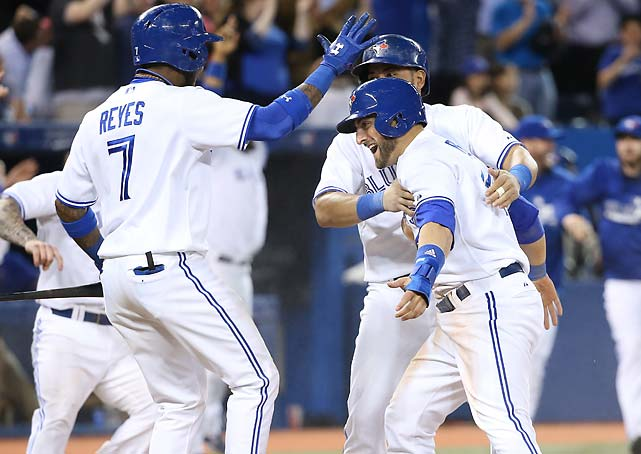 Kevin Pillar is embraced by Jose Reyes and Melky Cabrera after he scored the winning run in the ninth inning against the Tampa Bay Rays on May 28.