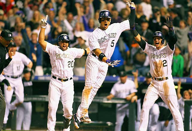 Wilin Rosario (20) and Troy Tulowitzki (2) celebrate as Carlos Gonzalez scores the game winner in the bottom of the ninth inning of a May 20 game against the San Francisco Giants.