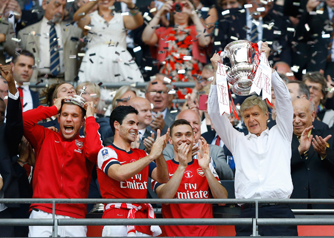 Arsenal manager Arsene Wenger, right, lifts the FA Cup trophy after guiding his club to victory over Hull City in the 2013-14 final.