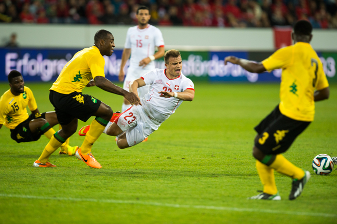 Switzerland's Xherdan Shaqiri gets tripped by Jamaica's Joel Grant and Wes Morgan in Friday's friendly.