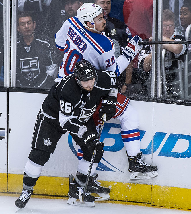 Slava Voynov of the Los Angeles Kings checks Chris Kreider of the New York Rangers into the boards