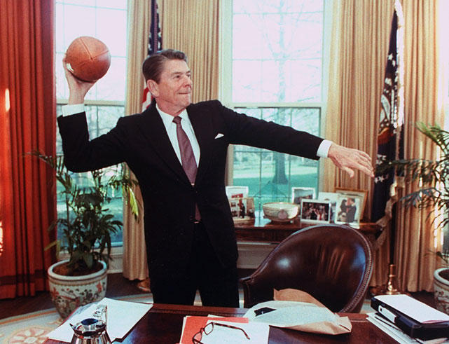 President Reagan throws a football from his desk in the Oval Office.