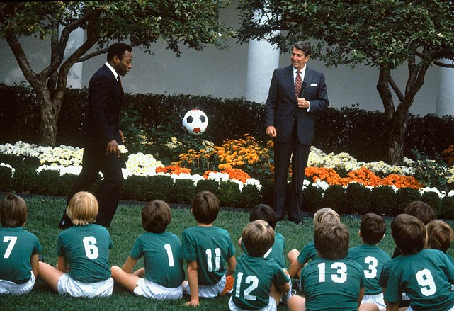 Pelé kicks a soccer ball around in front of a local boys' soccer team as President Reagan looks on in the Rose Garden at the White House.