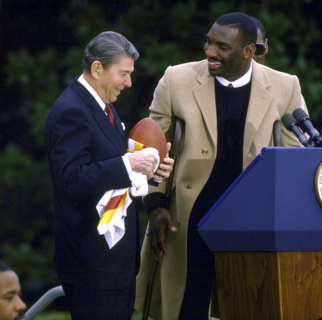 President Reagan receives a football and Redskins jersey from quarterback Doug Williams during a ceremony honoring the Super Bowl champion Washington Redskins at the White House.