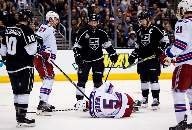 Dan Girardi lies in pain on the ice. He eventually went to the trainer's room with a bad hand.