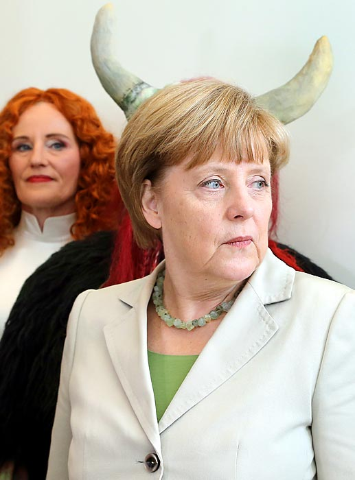 """Making like Maleficent, Germany's Chancellor welcomed the thespians of the """"Uckermaerkische Buehnen Schwedt"""" (roughly translated, we think, as <italics>Bob Uecker's Brewer Sweat</italics>) Theatre before a rollicking parliamentary meeting in Berlin. The actors, in turn, invited the Chancellor to attend an open air fantasy festival titled """"Der Fluch der Weissen Frau"""" (The Bane of the White Woman). Guten times!"""