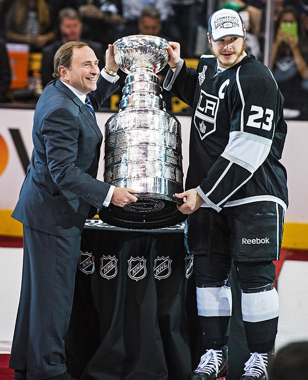 NHL commissioner Gary Bettman presents the cup to Dustin Brown.