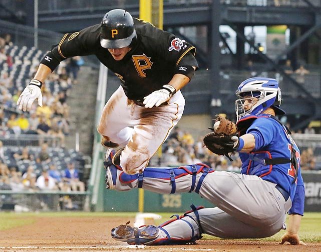 Chicago Cubs catcher John Baker tags out a leaping Clint Barmes of the Pittsburgh Pirates.
