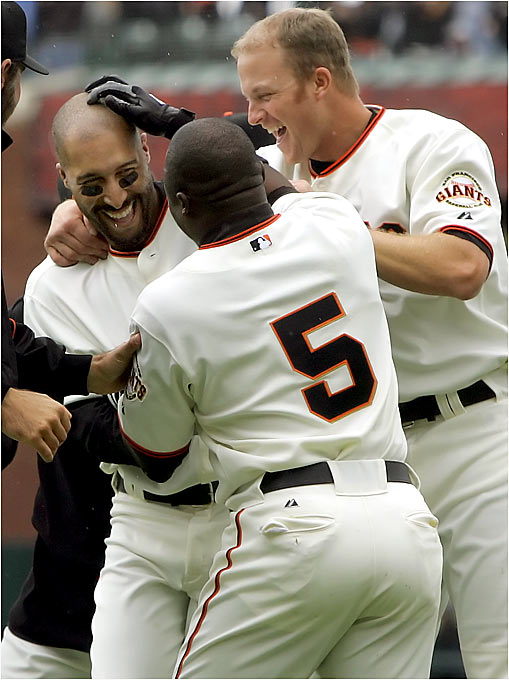 Giants outfielder Randy Winn is congratulated by his teammates after delivering the game-winning hit against the Braves on Sunday.