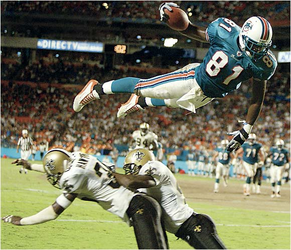 Miami Dolphins tight end Randy McMichael glides over a pair of New Orleans defenders to score during a preseason game in August 2002.