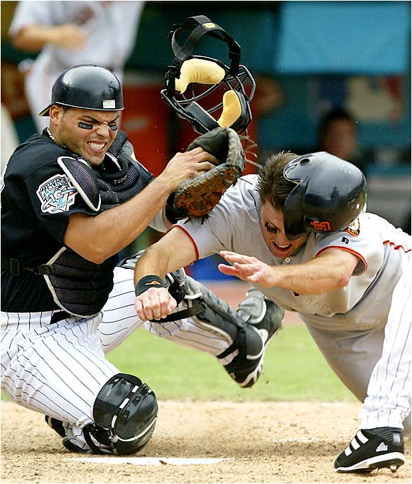 Florida Marlins catcher Ivan Rodriguez hangs on to the ball while being bowled over by J.T. Snow of the San Francisco Giants in Game 4 of the teams' 2003 NL divisional playoff series.