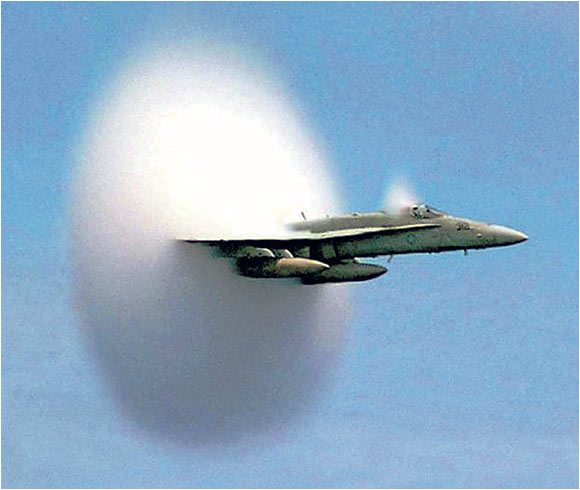 An F/A-18 Hornet emerges from a cloud caused when it broke the sound barrier in the skies over the Pacific Ocean in July 1999.