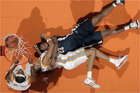 Tennessee's Candace Parker and UConn's Willnett Crockett crash to the floor after Parker scores a deuce.