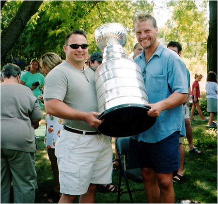 My best friend, Larry Van DeWater, is standing here with Shjon Podein and the Cup. The picture was taken at  Podein's celebration party in Minnesota after the Avalanche won the Cup in 2001. -- John Olszowka