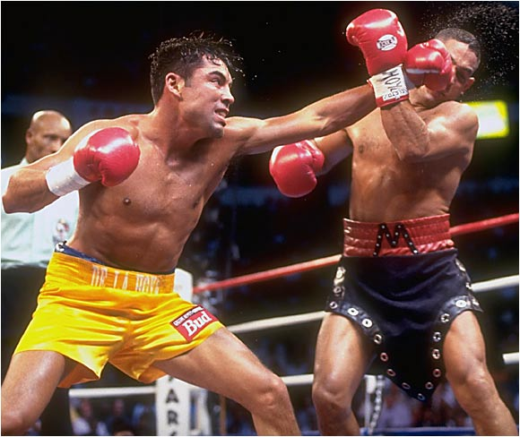 "Camacho entered the ring in a black-leather getup complete with visored helmet. He probably should have kept the headgear on, as the self-styled Macho Man was, at 35, past his prime and -- though ever the showman -- no match for the 24-year-old Golden Boy. De La Hoya pounded the elusive Camacho and, though he decked him in the ninth round, had to settle for a lopsided decision. ""He took some shots,"" said De La Hoya. ""I don't know how he stood up to them."""