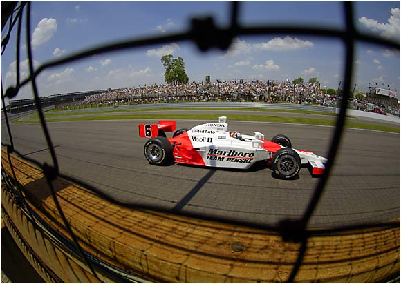 A peek through the protective barrier at Indy finds Sam Hornish Jr. racing to his first Indy 500 win.