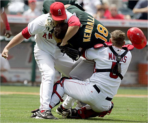 Angels pitcher John Lackey throws a haymaker at A's catcher Jason Kendall during this bench-clearing brawl in Anaheim last Tuesday.