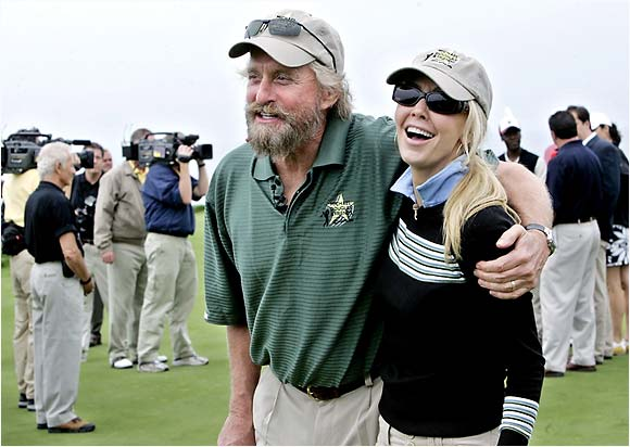Michael Douglas, evidently deciding to take the job in the next Grizzly Adams movie, shares a moment with fellow Hollywood celebrity Heather Locklear during Douglas' annual golf tournament.