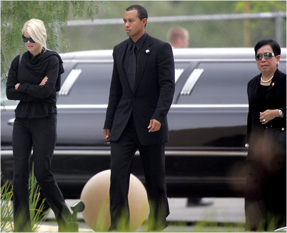 Tiger Woods, flanked by his wife and his mother, arrives at a reception following the burial service for his dad Earl Woods, who died last week after a battle with prostate cancer.